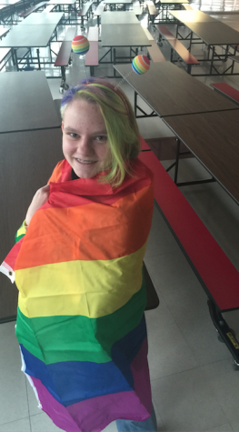 "Jenna Buraczewski, sophomore and cofounder of the GSA, wraps herself with the club's rainbow flag. The GSA reconvened on Nov. 13, 2014, for a new meeting to discuss LGBTQ issues in the media. Discussing her goals as a leader of the GSA, she stated, ""Honestly, as a leader of the GSA, I want my role as a leader to diminish as much as possible and I want to see the kinds in the club to take on the leadership roles."""