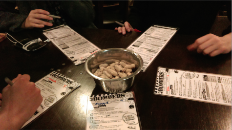 A group of friends fill out their menus as they enjoy complementary peanuts.