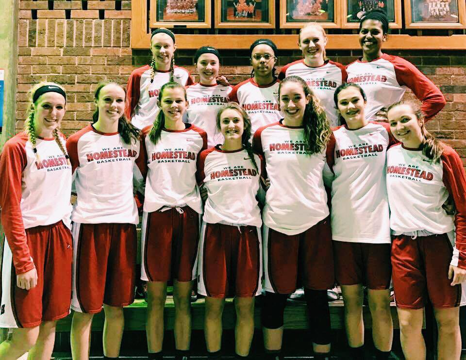 The girls varsity basketball team smiles for a photo.
