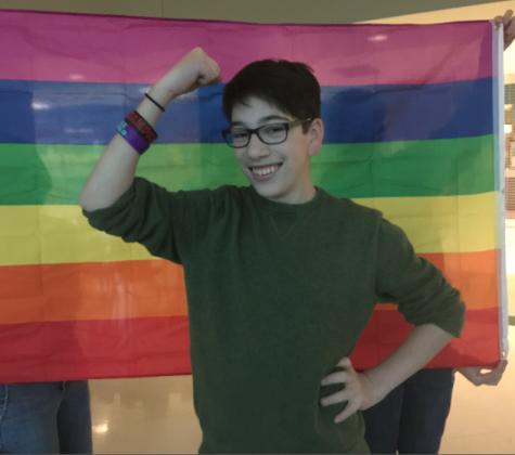 """Sam Ginkel, senior and cofounder of the GSA, strikes a pose in front of the club's rainbow flag. Gathering after the GSA's discussion of LGBTQ representation in the media on Nov. 13, 2014, various members and the leaders gathered together in the cafeteria to wind down and plan the topics of future meetings. Describing his goals as a leader, he explained, """"My goal is to create and help express LGBTQ topics and every other ordinary topic in a perfect blend just so that the GSA can reach a level of normalcy, so that anyone of any sexual orientation or gender identity just feels normal so they can talk about anything normally."""""""