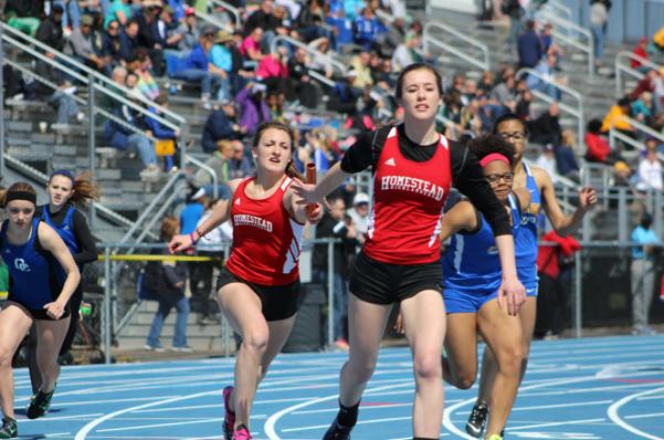 Savannah Melan, freshman, hands off the baton to Ellie Hetrick, junior, during the 4x200 relay on Saturday, April 11 at Nathan Hale High School.