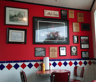 Red wall paper and wall tile keeps the atmosphere in Wayne's 50s and fabulous.