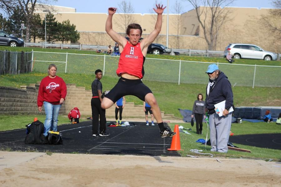 Jake Bruner, junior, competes in the Long Jump relay in which he helped the team place first in.