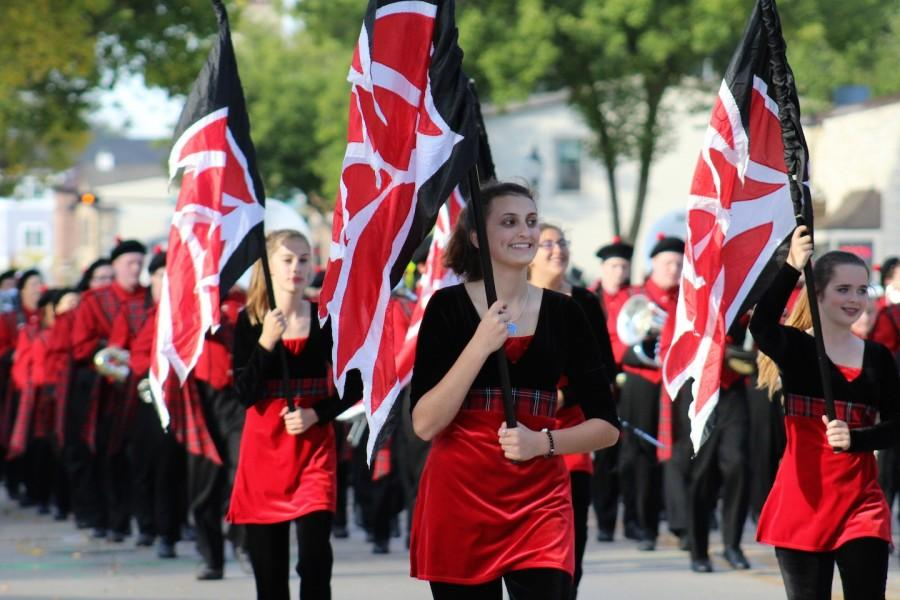 Sarah Sullivan, sophomore, takes in the sights and sounds of the Homecoming parade as a part of color guard.