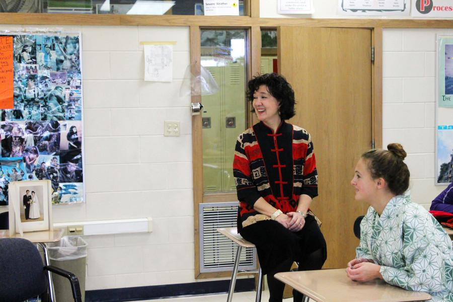 Ms. Grimm, social studies teacher, laughs along with her students during a lesson.