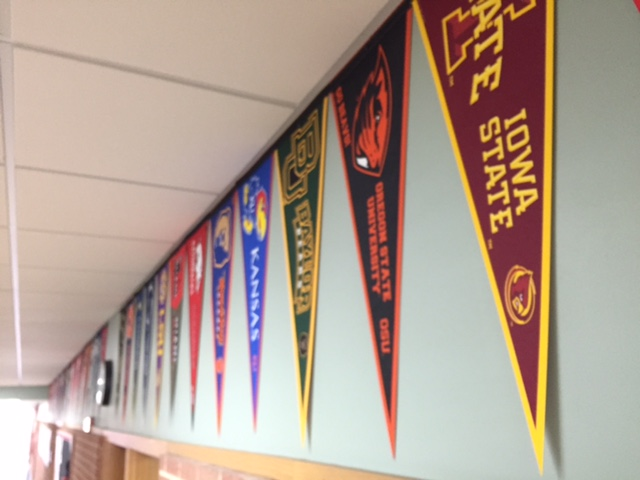 Hanging from several blank walls, college banners color the halls with school spirit. But do they also contribute to the pressure put on students to go to college? Photo by Erin Connolly
