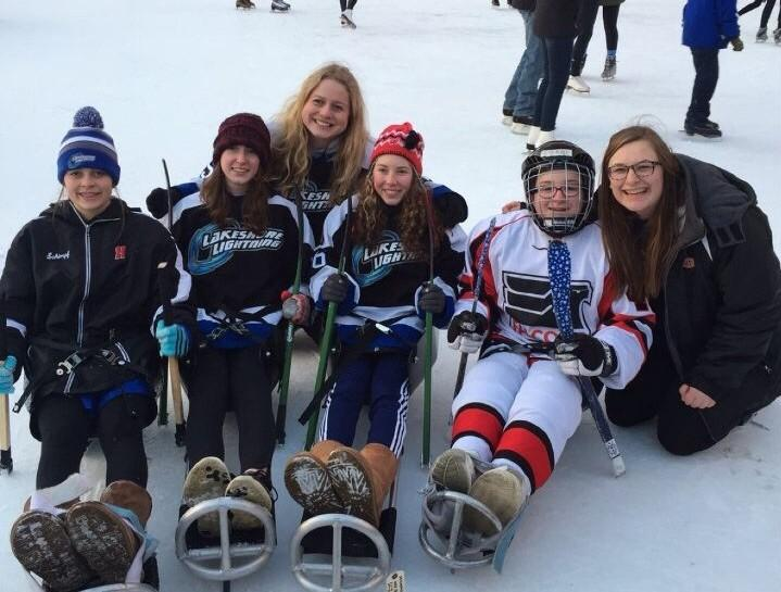 Lindsey Schimpf (far left) and Paige Weir (fourth from left) try out the sleds with their new friend Gabbi.