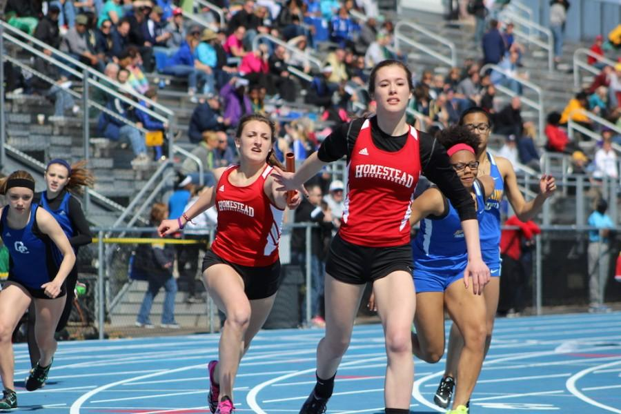 Ellie Hetrick, Senior, receives a hand off from Savannah Melan, Sophomore in the girls 4x200 meter relay. The relay team consisted of Hetrick, Melan, Grace Karegennas, Junior, and Mary Kate Simon, Senior and placed second.