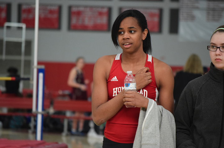 """Leah Gholson, junior, takes a breather after her event. Gholson was the starting runner for her relay on Thursday. """"I really just do track for the fun of it,"""" Gholson said."""