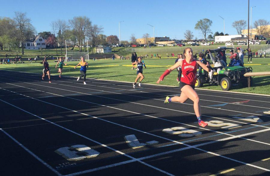 Alex Burns, senior, crosses the finish line ahead of everybody in the girls 4x100 meter relay.