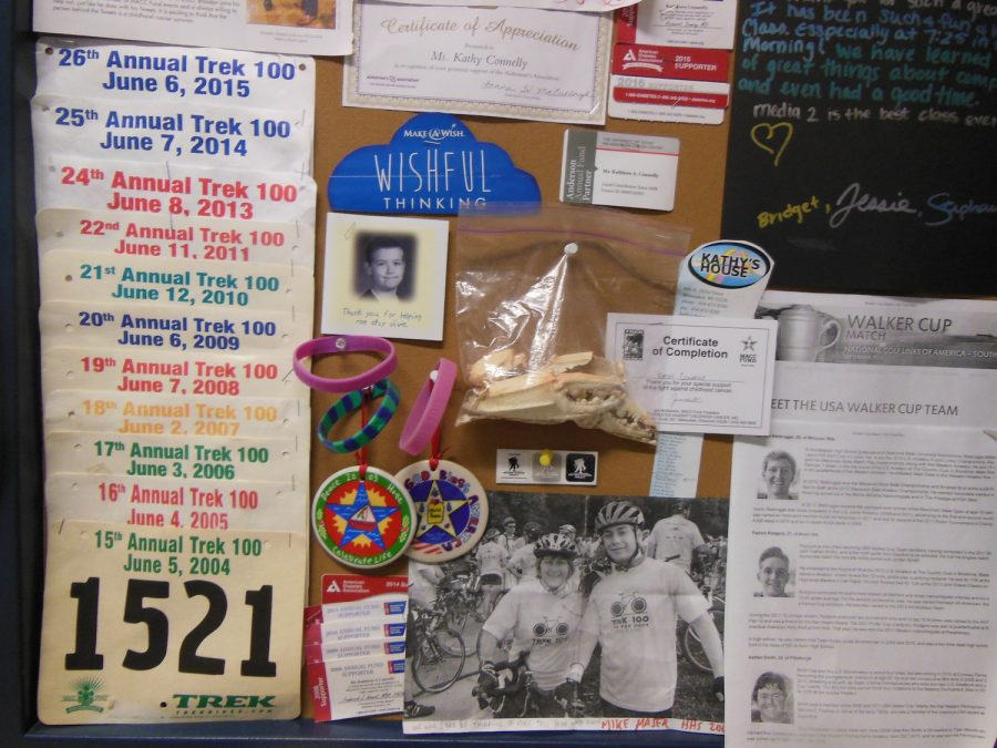 """The cork board on Mrs. Connelly's wall has over a decades worth of Trek 100 bib numbers. To the right of the bibs are certificates, letters, and pictures from the Trek 100 rides, founded by the M.A.C.C fund, that Mrs. Connelly has participated in. """"All these kids are amazing, just amazing. They're the reason I keep riding,"""