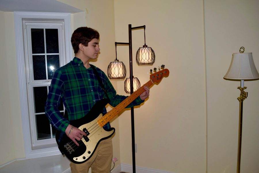 Will Slawson, junior, plays a song on the bass. Slawson has played the bass for many years and it is one of the ways he copes with the adversity he has faced.