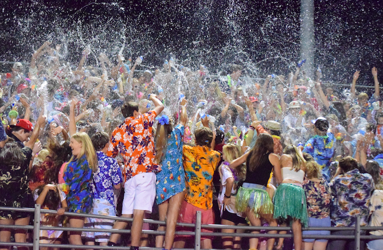 """The Homestead student section throws water at half time. The students came dressed in Hawaiian clothes for the luau themed game. """"I wouldn't want to belong to any other student section,"""" Skylar Pak, senior, said."""