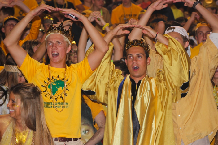 Matthew Klimkosky (left) and Sam Gianakos (right) cheer on the football players during the game on Friday, Sept. 16.  Klimkosky and Gianakos chose gold as the theme for the game in support of September's childhood cancer awareness month.