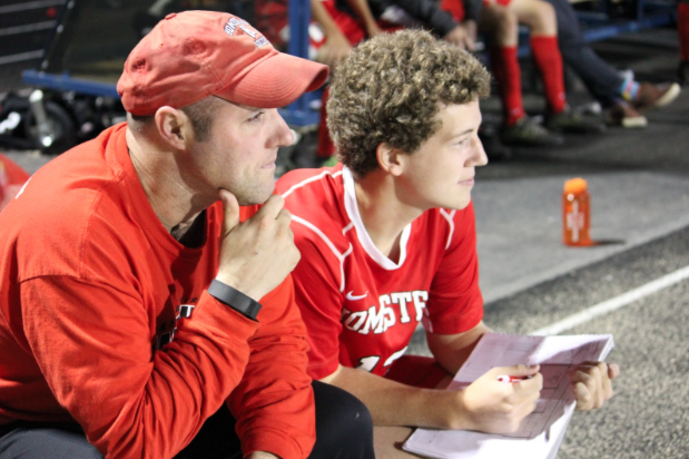 Collin Reiels, senior, sits alongside Coach Tony Navarre at the boys soccer game on Friday.