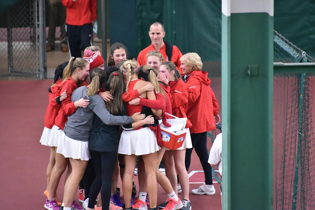 The girls varsity tennis team hug after winning state. The girls were undefeated throughout their entire season.