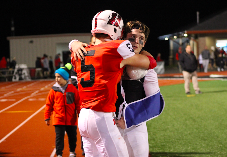 Brad Woldt, junior, embraces Eric Zoeller, senior, after his injury. Despite Zoeller not being able to finish the game, the boys still defeated Whitefish Bay and moved on to the semifinals.