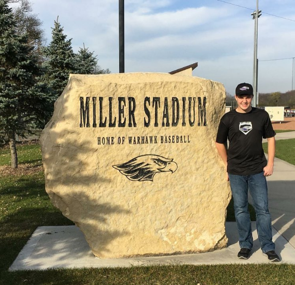 Panella stands next to Whitewaters baseball stadium sign.
