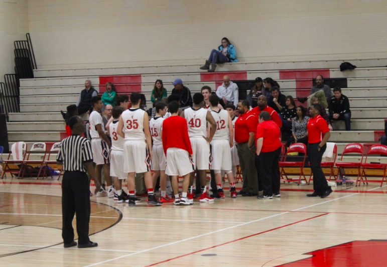The+boys+varsity+basketball+team+huddles+during+home+game+against+Wisconsin+Lutheran.