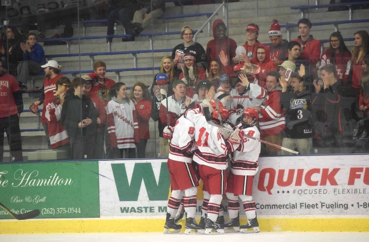 The hockey team celebrates after winning a game.