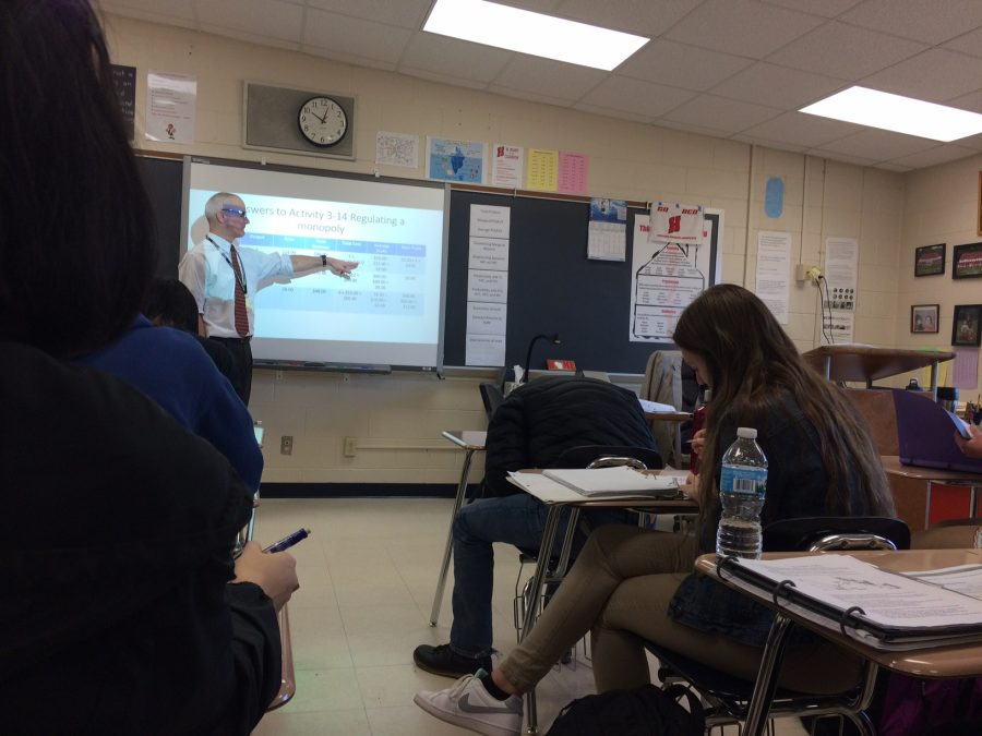 Mr. Tom Fugate teaches his economics class while Mrs. Susan Lueders, his former department chair, attends his class first hour each day.