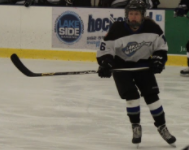 Paige Weir, number 16 on the ice, keeps a close eye on the puck.