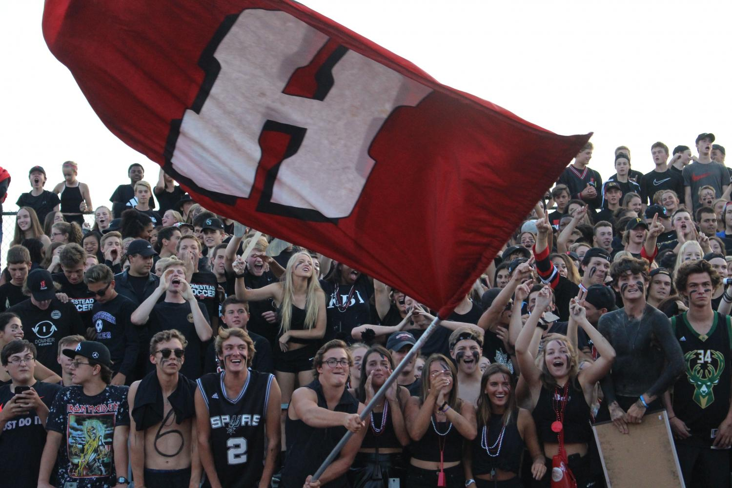 .+The+Homestead+student+section+cheers+for+the+football+players+while+encompassing+the+black+theme.