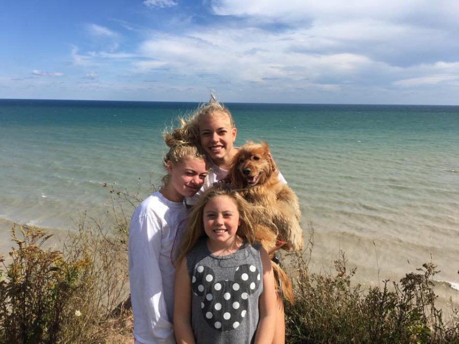 Grace+Baden%2C+junior%2C+joyfully+holds+her+dog+while+standing+along+her+two+smaller+sisters+in+front+of+Lake+Michigan.