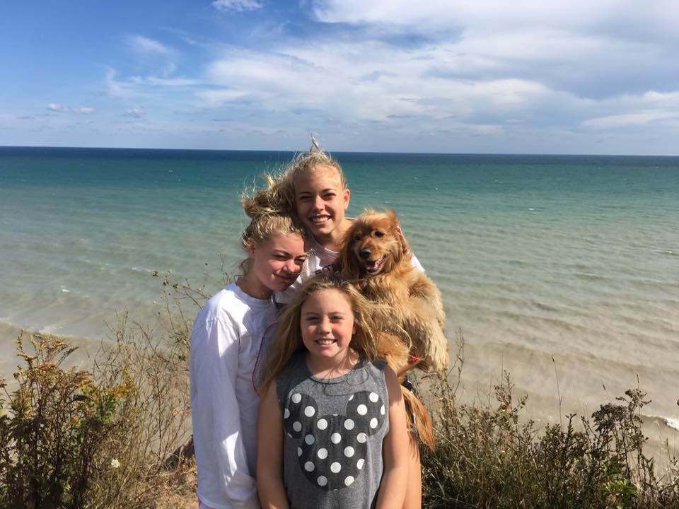 Grace Baden, junior, joyfully holds her dog while standing along her two smaller sisters in front of Lake Michigan.