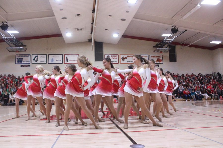 The dance team forms a dynamic triangle with synced choreography to end their routine.