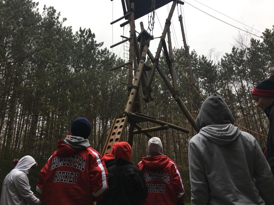 The Homestead hockey players watch their teammates battle through the arctic climb ropes course.