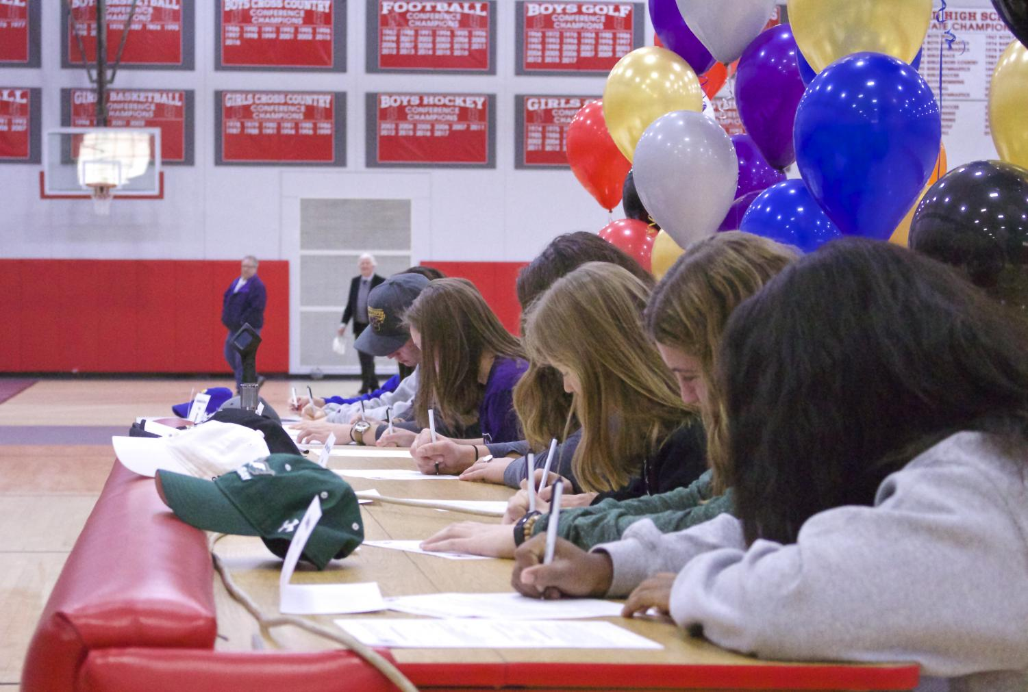 The athletes sign their papers to commit to their schools.