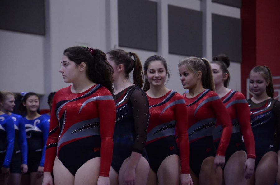 The+girls+gymnastics+team+lines+up+at+the+start+of+the+meet.