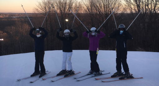 Freshmen Andrea Schwalbach, Katie Quasius, Amanda Odem, and Ava Mcnarney lift their poles in the air before skiing down the hill on Feb. 4.