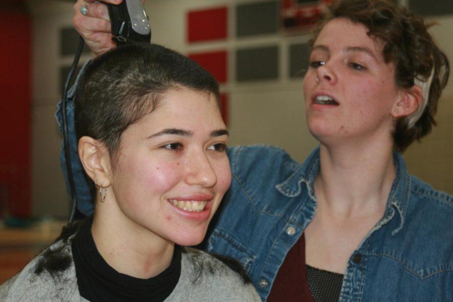Emma Rachum, senior, smiles as Lily Norman, junior, buzzes off her hair.