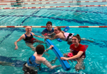 Anna Lalande and Hannah O'Brien, juniors, and Savannah Melan, senior, enjoy their time splashing around with the students in their adaptive physical education class.