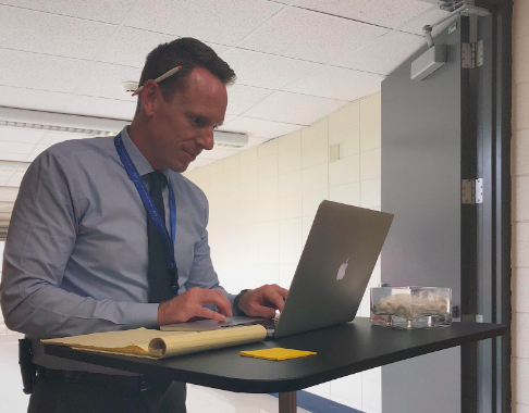 Principal Brett Bowers reads emails at his new rolling desk, newly outfitted with fresh mints for visitors.