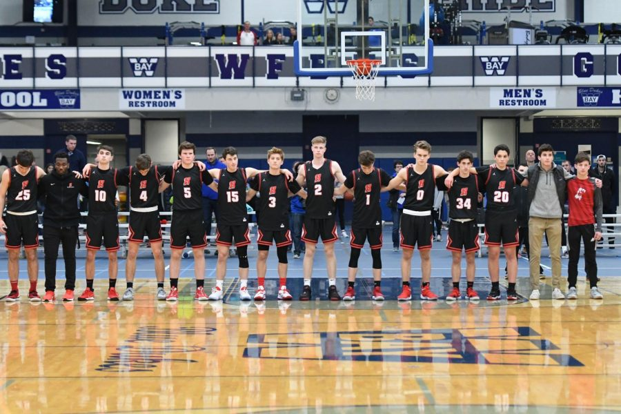 Homestead Boys Basketball team together for the national anthem at Whitefish Bay High School.