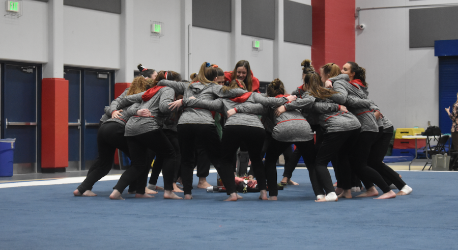 The+gymnastics+team+huddles+to+pump+themselves+up+for+their+last+home+meet.