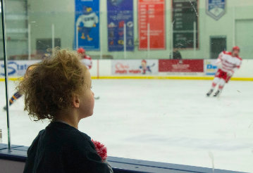 Cayden Navarre attentively watches his dad coach the boys varsity hockey game.