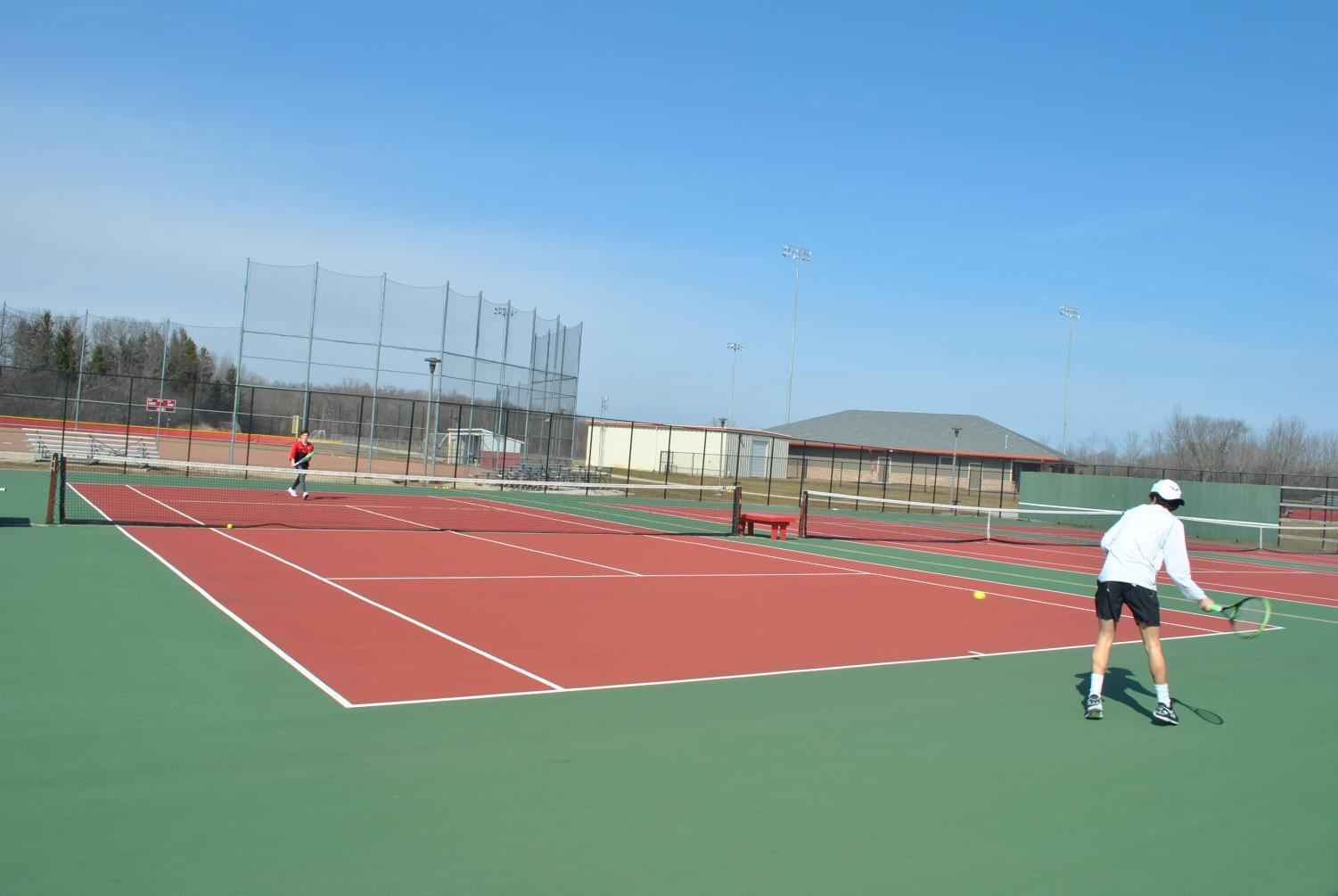 Zach Sprinkmann (left), sophomore, and Eli Eiseman (right), senior, warm up before the final day of tryouts.