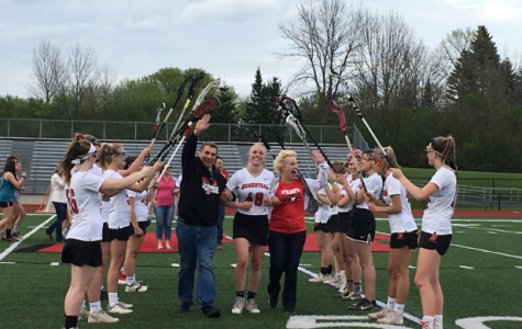 Anna Lalonde, senior, is welcomed by her team with her parents on her side celebrating senior night.