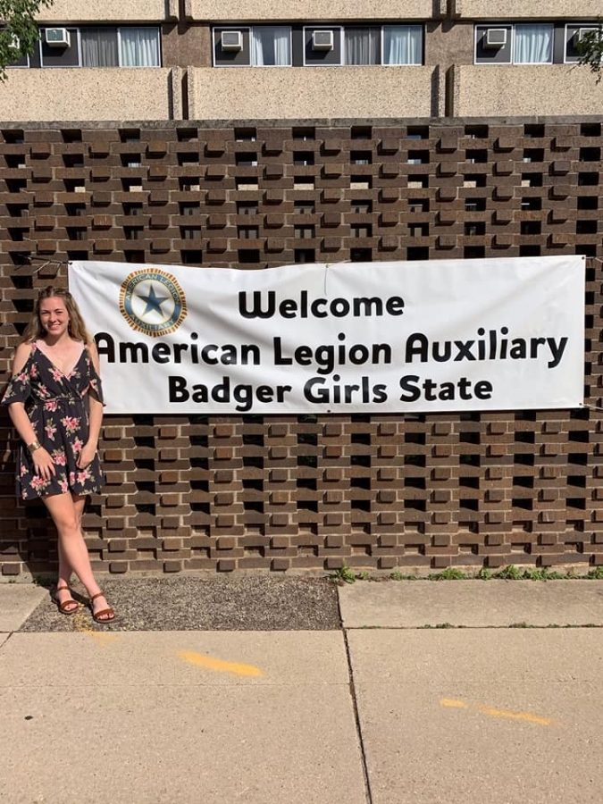 Bridget Brown, senior, smiles while standing next to the welcome sign