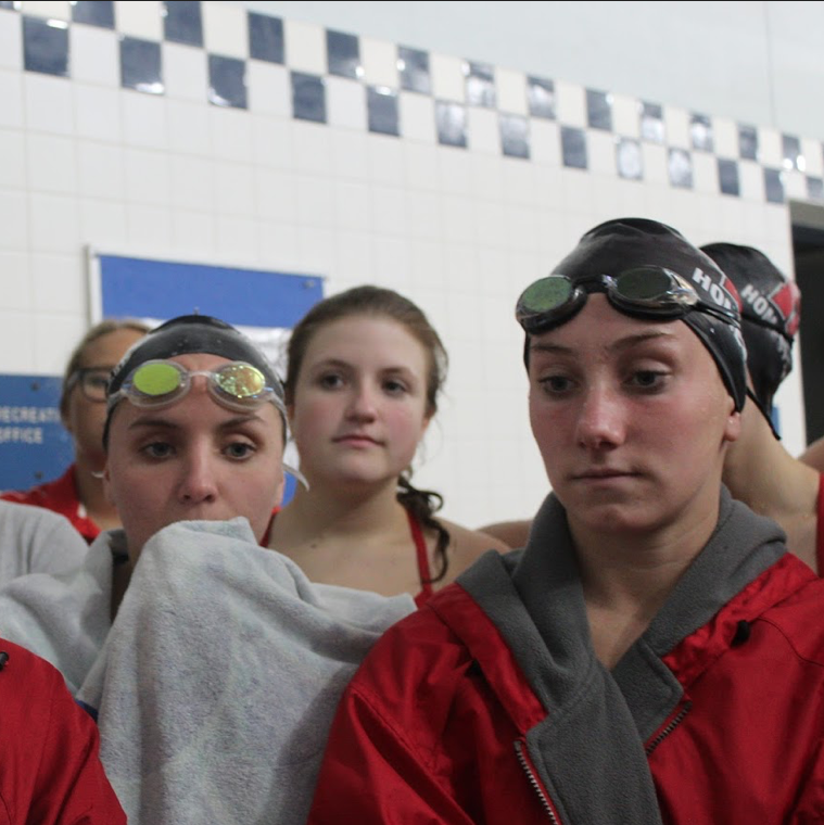 Cat+Seiberlich%2C+Hannah+Tracy%2C+and+Katie+Lennie%2C+seniors%2C+listen+to+their+coach+give+a+speech+between+events.+