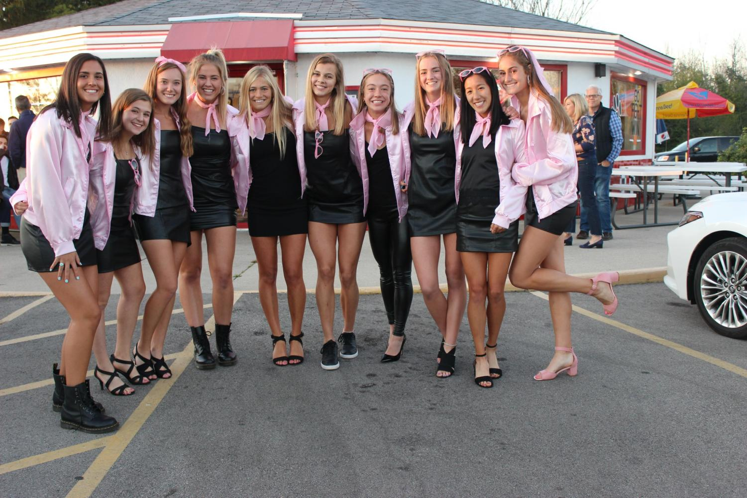 Mia Patel, Anna Gilgur, Madison Heitz, Kitty Nelson, Annie Gebhardt, Grace Mueller, Ava Wojnowski, Megan Carley, Natalie Yang, and Lauren Fitzsimmons, seniors, pose in their Pink Ladies from Grease costume