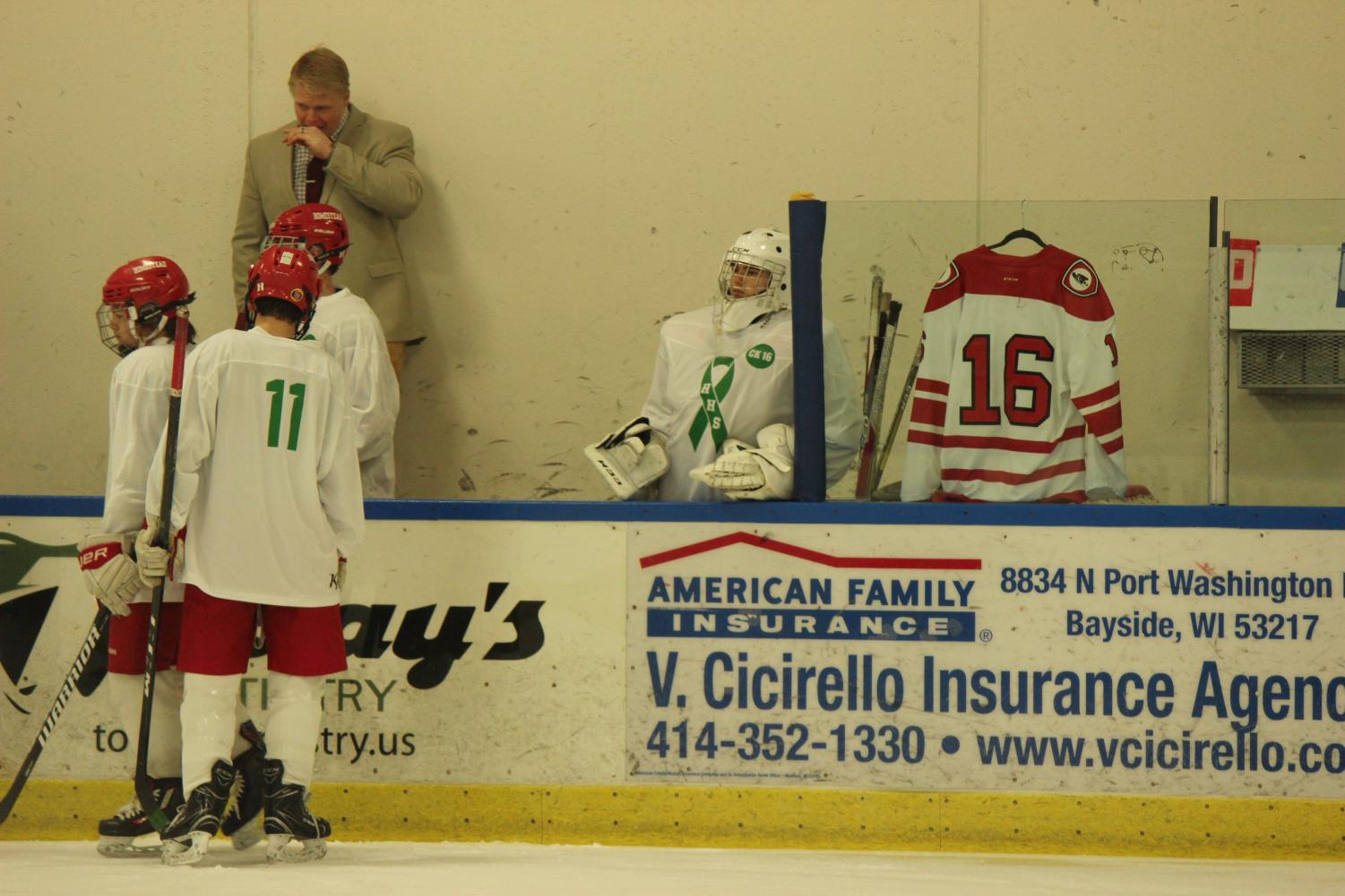 Jersey #16 is displayed through the glass on the ice rink during the game in remembrance of Cam Kranich.