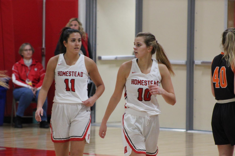 Grace Mueller and Mia Patel, seniors, walk back on defense.