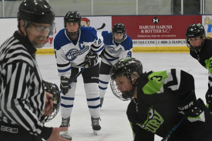 """Amy Erpenbeck, senior, focuses on the puck before a face-off. Erpenbeck has been on the team since freshman year. """"It's so much fun being able to spend almost every day with the team and continue to grow as a player,"""" Erpenbeck said."""