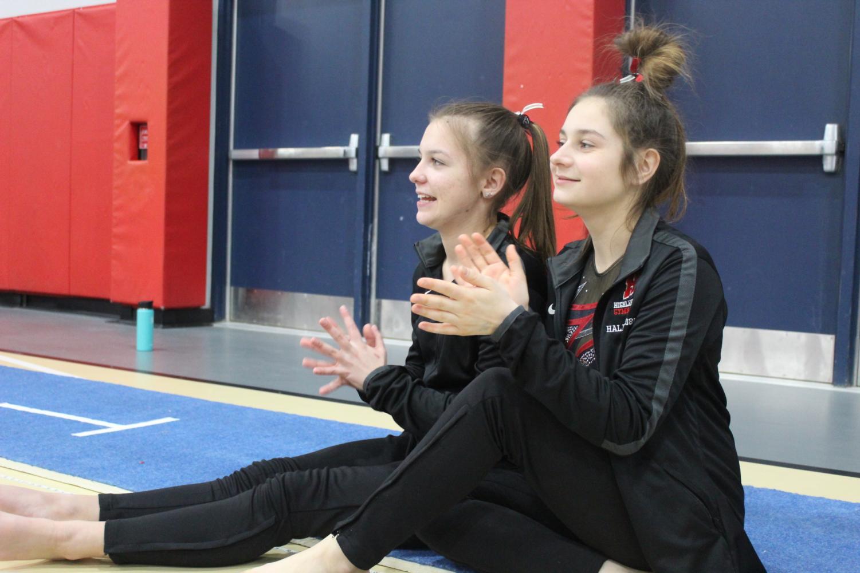Eileen Tylets, senior, and Ari Halaska, junior, cheer on their teammates during competition.