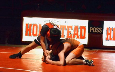 Cole Movessian, sophomore, pins his opponent to finish his match for a Highlander win.